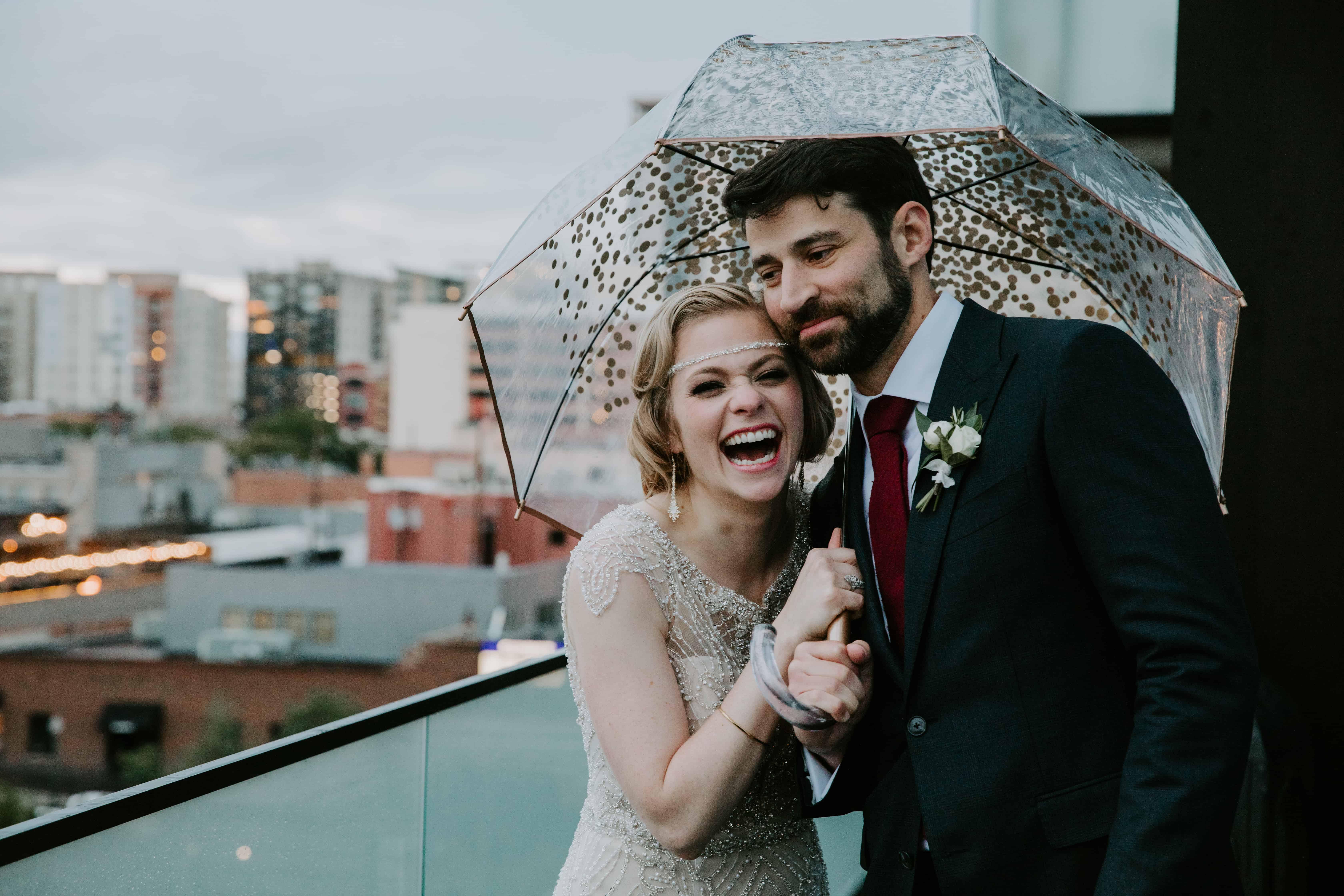 Happy bride and groom in urban Denver outdoor wedding venue in the rain