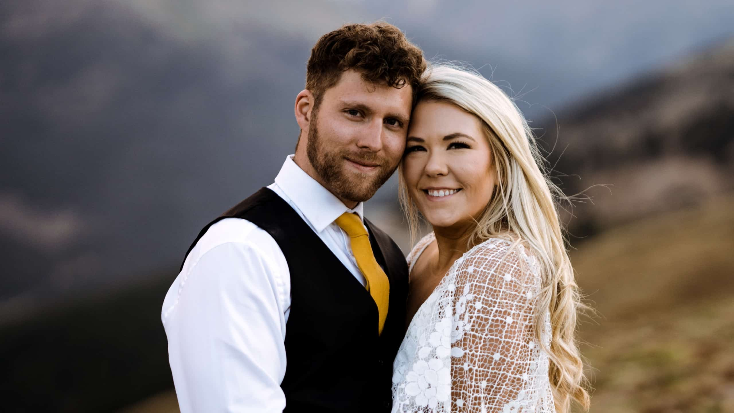 Bride and groom smile on mountaintop elopement