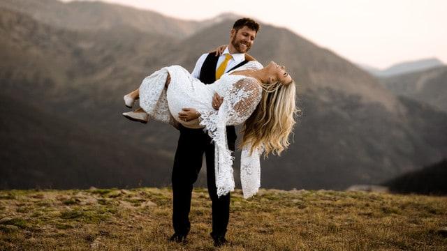 Groom carrying bride in mountain top