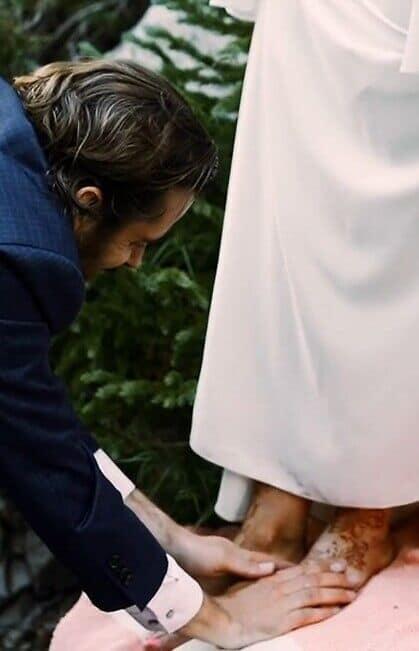 Groom washing bride's feet in footwashing ceremony
